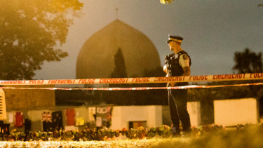 A policeman stands guard at the Al Noor Mosque early on Friday morning.
