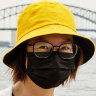 A tourist from Hong Kong wears a mask in Sydney as a precaution against coronavirus. on Wednesday.