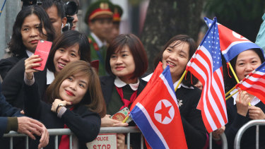 Young Vietnamese pose for a selfie outside the Hotel Melia in Hanoi while waiting for Kim Jong-un.