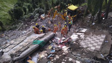 Rescuers look for survivors after a three-story building collapsed in monsoon rains near the town of Solan, India.