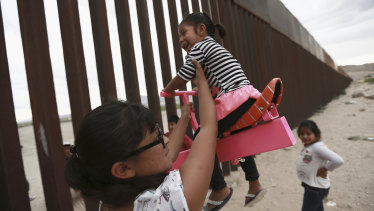 A woman helps her girls play on a seesaw installed between the border fence that divides Mexico from the United States in Ciudad de Juarez, Mexico.