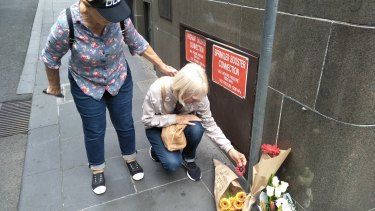 Cheryl Page and Dianne Davies left a red poppy as a tribute on Bourke Street on Saturday.