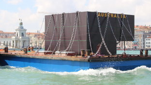 In Richard Bell's disruption, a model of the Australian pavilion at the Venice Biennale is chained on a barge.