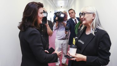 Senator Jane Hume speaks with the March 4 Justice organiser Janine Hendry in a hallway at Parliament House.
