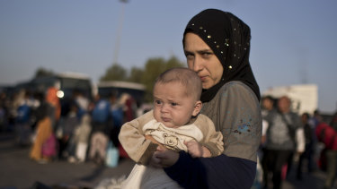 Nermi Zeitoun, 19, from Idlib, Syria, holds her three-month-old son after they disembark   at the port of Piraeus on Tuesday. Nermi was one of 400 migrants deemed vulnerable and removed from the Moria camp on Lesbos.
