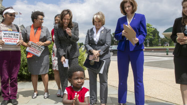A child of an immigrant joins applause as Senator Kamala Harris, joined by Governor Michelle Lujan Grisham and Senator Catherine Cortez Masto, protest against threats by President Donald Trump against asylum seekers in 2018.