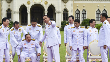 Reflecting the culture: Thai Prime Minister Prayut Chan-o-cha assists his Deputy Prime Minister General Prawit Wongsuwan during a group photo after cabinet reshuffle at Government House in Bangkok last month.