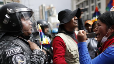 Protests continue: A supporter of Bolivia's former president Evo Morales yells at a police officer to respect the nation's indigenous people in La Paz, Bolivia.