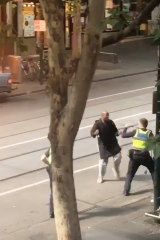 Police confront the alleged attacker on Bourke Street.