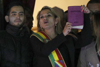Jeanine Anez, wearing the Presidential sash and holding a Bible, addresses a crowd from the balcony of the Quemado palace after she declared herself interim president of Bolivia in 2019.