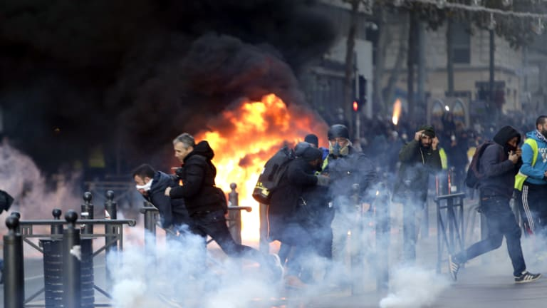 People run from a burning car during clashes with police on  Saturday in Marseille, southern France.