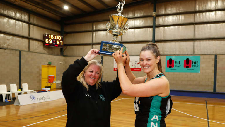 Kim Symons and Fiona Morrissey lift the State League trophy.