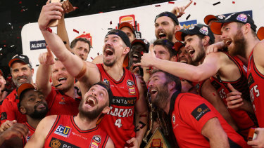 Wild times: Perth's Greg Hire takes a team selfie with the trophy after claiming the NBL championship on Sunday.