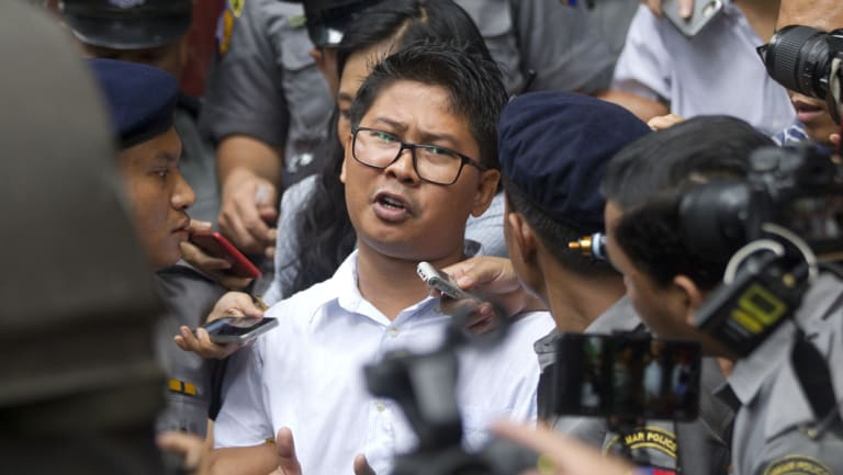 Reuters journalist Wa Lone, centre, talks to journalists as he is escorted by police when leaving the court on Monday in Yangon, Myanmar.