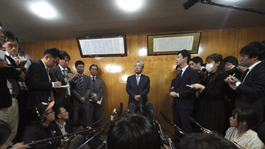 International Olympics Committee member and head of the Japanese Olympic Committee Tsunekazu Takeda, centre, speaks to journalists after a JOC executive board meeting in Tokyo on Tuesday.