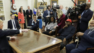 President Donald Trump talks to NFL Hall of Fame football player Jim Brown, seated right, and Rapper Kanye West, seated center, and others in the Oval Office of the White House.