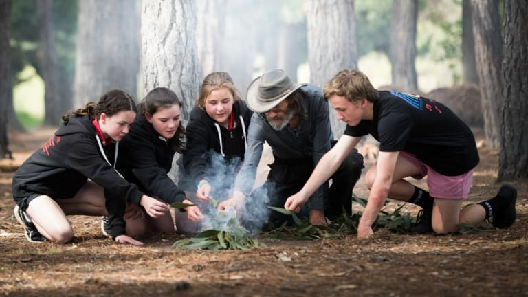 Dixons Creek Primary school students Chloe, Lily, Shanice and Connor with Wurundjeri elder   Uncle Dave Wandin, who's been teaching children about Indigenous burning techniques.
