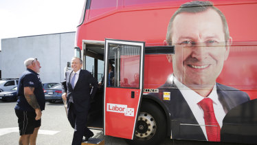 Opposition Leader Bill Shorten exits the campaign bus featuring the face of WA Premier Mark McGowan during his visit to the Volgren bus facility in Perth on Wednesday.