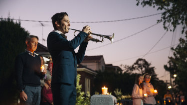 Albie Woodhouse plays The Last Post on trumpet for a driveway dawn service .