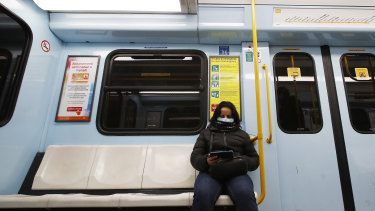 A woman wearing a face mask checks her phone in a subway carriage in Milan, Italy.