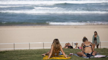 People sit beside a closed Bondi Beach on Friday afternoon.