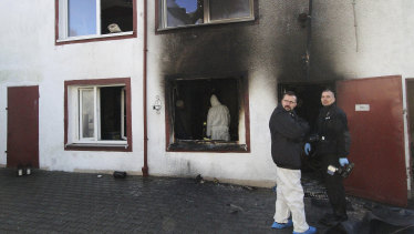 Forensic and police experts examine the site of a fire in an escape room in Koszalin, Poland.