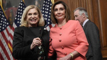 House Speaker Nancy Pelosi stands with House Oversight and Government Reform Committee Chair Representative Carolyn Maloney, left, after she signed the resolution to transmit the two articles of impeachment against President Donald Trump to the Senate for trial on Capitol Hill in Washington.