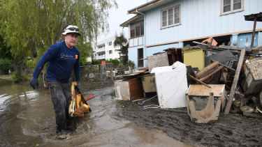 Chris Mitchell removes flood damaged items out of his father in-law's house in the Townsville suburb of Rosslea.