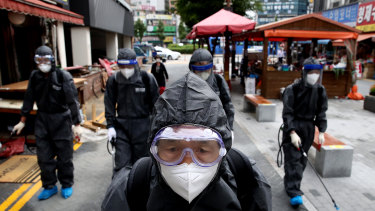 Health officials from Incheon, South Korea, wear spray anti-septic solution in an alley of markets and shopping district.