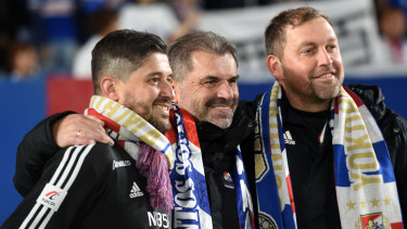 Papas, left, celebrates Yokohama F. Marinos' title win last season with Ange Postecoglou and Peter Cklamovski.