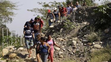Venezuelans cross into Colombia illegally near the Simon Bolivar International Bridge in La Parada on Monday.