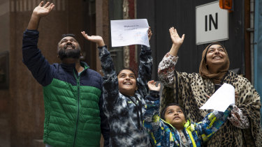Maruf Ahmed and Sabrina Abbasi and their children wave to Maruf's parents in quarantine at the Raddison Blu.