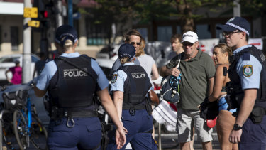 Police move people on at Coogee Beach on Saturday, when beaches were open for exercise between 6am and 9am.