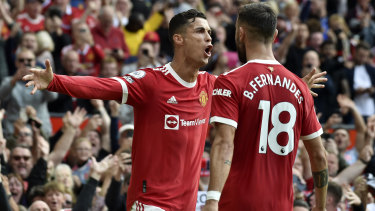Cristiano Ronaldo celebrates with Portuguese teammate Bruno Fernandes after scoring the opening goal of the English Premier League match between Manchester United and Newcastle United at Old Trafford.