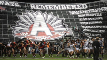 Both sides running through the ANZAC banner before the game.