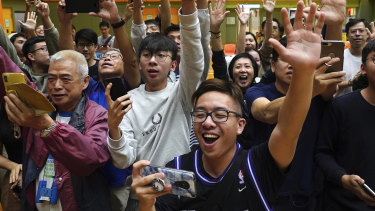 A big night for democracy in Hong Kong. Supporters of pro-democracy candidate Angus Wong celebrate after he won in district council elections.