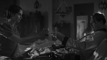"""The entire film is shot in shadowy black and white: Lily Collins and Gary Oldman in 'Mank""""."""