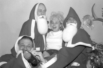 In this 1963 photo, British comedians Sid James, left, Hughie Green and Dickie Henderson, right, carry British actress Barbara Windsor during the Variety Club of Great Britain Christmas luncheon at the Savoy Hotel in London.