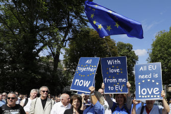 Anti-Brexit demonstrators join Beatles fans, with signs of Beatles songs, to walk across Abbey Road last week.