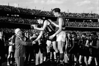 Hawthorn captain, Graham Arthur, is presented with the 1961 Premiership Cup.