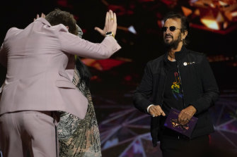 Finneas bows toward presenter Ringo Starr as he goes on stage to accept the award for record of the year for Billie Eilish's Everything I Wanted.