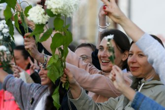 Women wave flowers as they join the fifth day of protests against Sunday's election results.