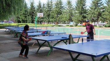 Tumen citizens play ping pong in a park.