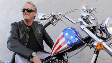 Peter Fonda, poses atop a Harley-Davidson motorcycle in 2009.