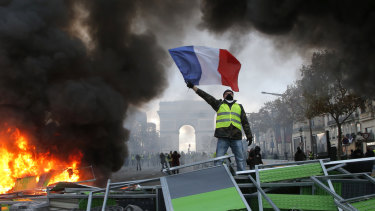 A demonstrator waves the French flag on a burning barricade on the Champs-Elysees with the Arc de Triomphe in the background, during a demonstration against the rise of fuel taxes.