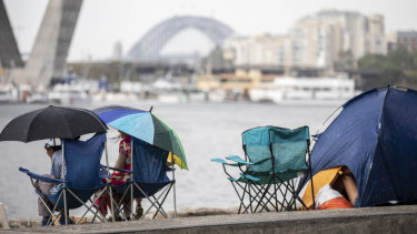 New Year's Eve revellers gather under shelter during the afternoon storm at Glebe Foreshore.