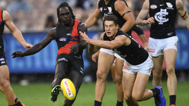 Tipping point: Anthony McDonald-Tipungwuti kicks on despite pressure from Carlton's Liam Stoker.
