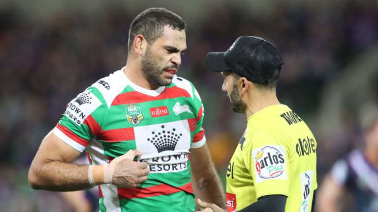 That's the spot: Greg Inglis discusses his rib cartilage injury with a trainer on Friday night.