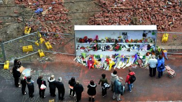 People pay tribute to the three victims at the site of the Swanston Street wall collapse in April 2013.