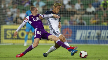 Firing on all cylinders: Melbourne's Keisuke Honda battles for possession with Neil Kilkenny of Perth.